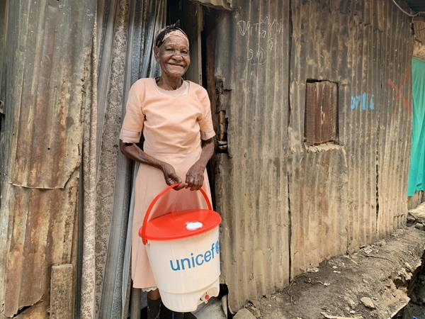 Old woman smiles after receiving a bucket for handwashing